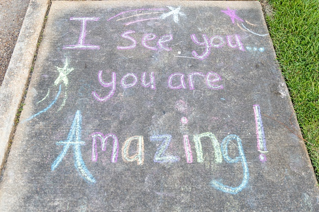 image of message written for kids on concrete pavement chalk