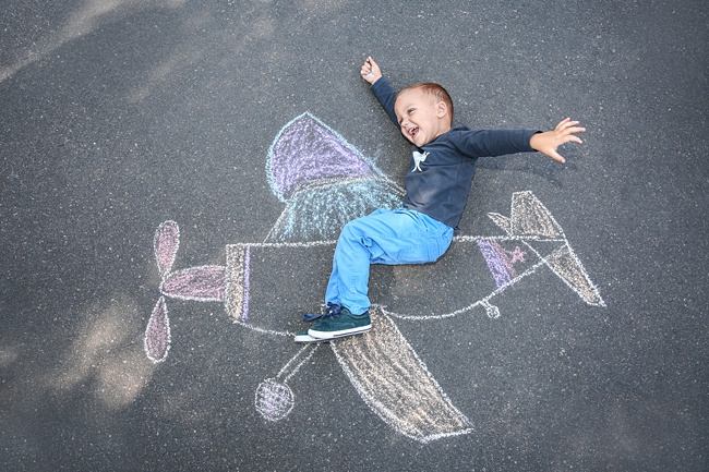 image of pavement chalk drawing child on patio having fun